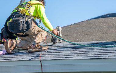 A man works on repairing a roof with wesfall roofing