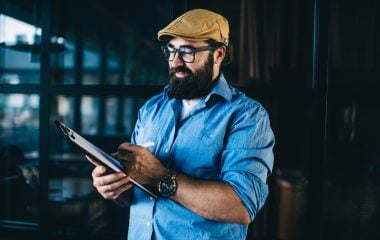 Cheerful bearded mature male architect satisfied with creating plan and sketches holding planner, positive business mindset